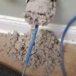 Dryer lint being removed from vent duct with rotary brush tool
