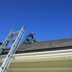 Eddie Kyles cleaning a dryer vent cap on a roof top